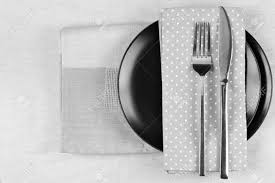 table setting black plate fork and knife with napkins on linen