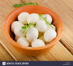 small balls of mozzarella in bowl selective focus stock photo