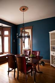 dark teal wall paint and unpainted wooden trim for the dining room