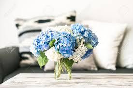 interieur et canapé bouquet de fleurs hortensia sur une table basse en bois modernes et