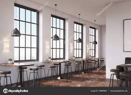 coffee shop interior with a large sofa near a white wall a row of