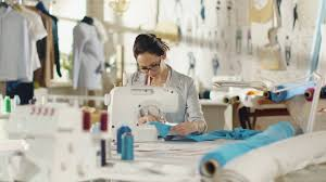 his and items fashion designer dressmaker working on a sewing machine in