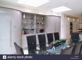 modern open plan kitchen dining room black leather chairs and glass table in modern open plan dining