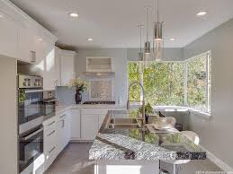 contemporary kitchen with breakfast bar by brandon johnson contemporary kitchen with timeless white 3x12 glass wall tile artika ampere champagne glow indoor pendant