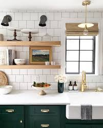 white tile open shelving farmhouse sink and dark green lower