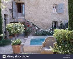 French Country House by Small Tree In Terracotta Planter And Wicker Armchair In Courtyard