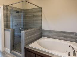 the master bath features a large soak tub and separate shower shower doors