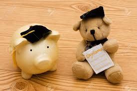 graduation piggy bank a piggy bank and a wearing graduation caps on a wooden