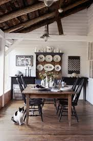 rustic country dining room with wooden table and black chairs