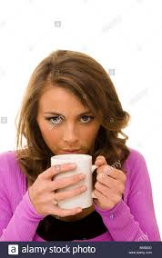 woman blowing across the top of a cup of coffee tea stock photo