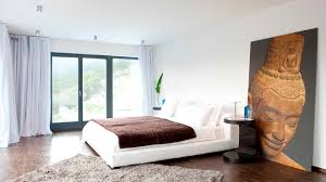 interior white bed with brown quilt near large painting beautiful