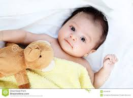cute baby boy is happy with yellow blanket and bear