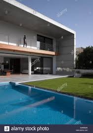 house with swimming pool man walking along double height balcony facade of d house with