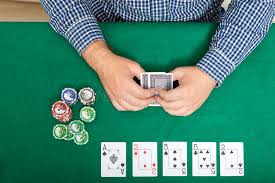 poker table top and chips chips and cards for poker in hand on green table top view stock