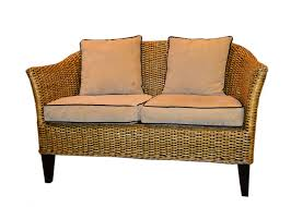 outdoor natural wicker loveseat with black legs and cushion for