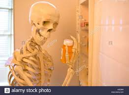 skeleton takes drugs from the medicine cabinet spooky stock photo