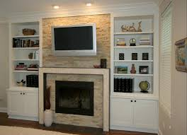 cream fireplace with television above between white wooden shelves