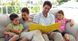 Cute Family Relaxing Together On The Couch Looking At Photo Album - Family in living room
