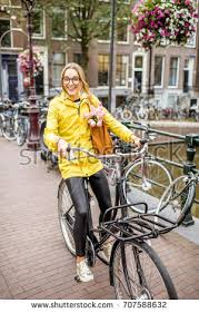 raincoat for bike riders young woman yellow raincoat bag flowers stock photo 707588731