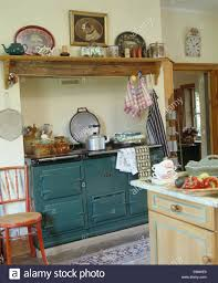 wooden shelf above green aga in traditional country kitchen stock