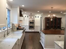 historic kitchen with carrara marble perimeter countertops and a historic kitchen with carrara marble perimeter countertops and a butcher block island white subway tile