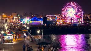 California destination travel images Drone footage santa monica pier illuminated night tourists ferris jpg