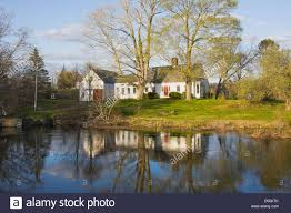 Cape Cod Style Home by Cape Cod Style House Reflecting In Stream Spring Maine Stock Photo