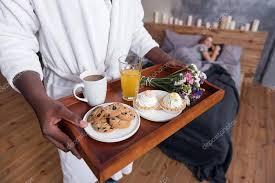 chambre et petit dejeuner homme africain tenant le plateau avec le petit déjeuner en chambre
