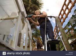 woman mending fences and repairing outside of house stock photo