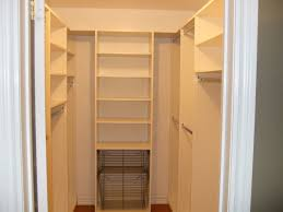 small walk in closet in white theme featured wall shelves and two
