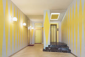 yellow entryway to this home in milan with carrara marble floors