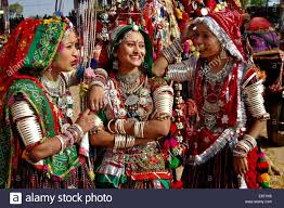 three performers in traditional indian dresses and ornaments