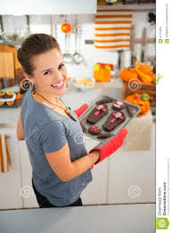 woman removing from oven tray with homemade halloween cookies