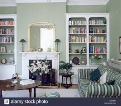 fitted white bookcases on either side of fireplace in gray green