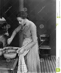 profile of a young woman cooking food in the kitchen stock photo