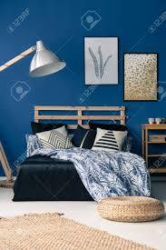 chambre osier chambre bleu foncé avec meubles en bois et pouf en osier