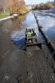 worker in a small bulldozer excavating canal mud pipeline