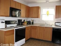 l shaped brown wooden kitchen cabinet with white countertop on