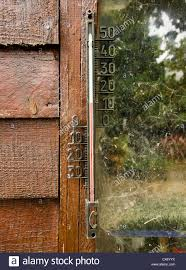 an outdoor thermometer hanging on the wall of a wooden garden shed