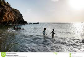teens and kids playing on water ocean scenery black volcanic