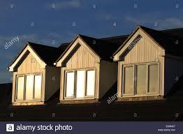 three dormer attic windows reflection in the evening sun two