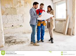 young couple looking blueprints of their home with handyman stock