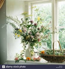 Kitchen Windowsill Still Life Of Vase Of Summer Country Flowers On Kitchen Windowsill