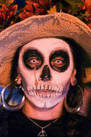 woman with skull makeup white contact lenses día de los muertos
