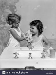 1930s bathroom 1930s two girls sisters at bathroom sink stock photo royalty free