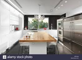 modern black and white kitchen black and white kitchen with wooden dining table in modern villa