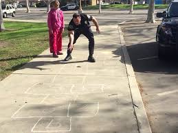police officer teaches homeless to play hopscotch in