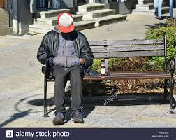homeless man sleeps on a bench in the city stock photo royalty
