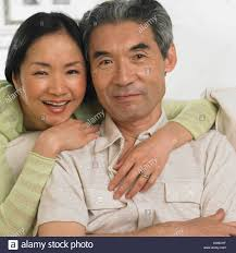 middle aged middle aged asian couple hugging and smiling stock photo royalty