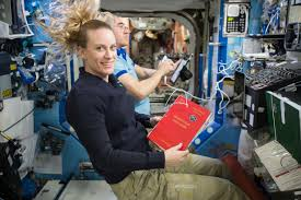 astronaut kate rubins holds a reference guide nasa